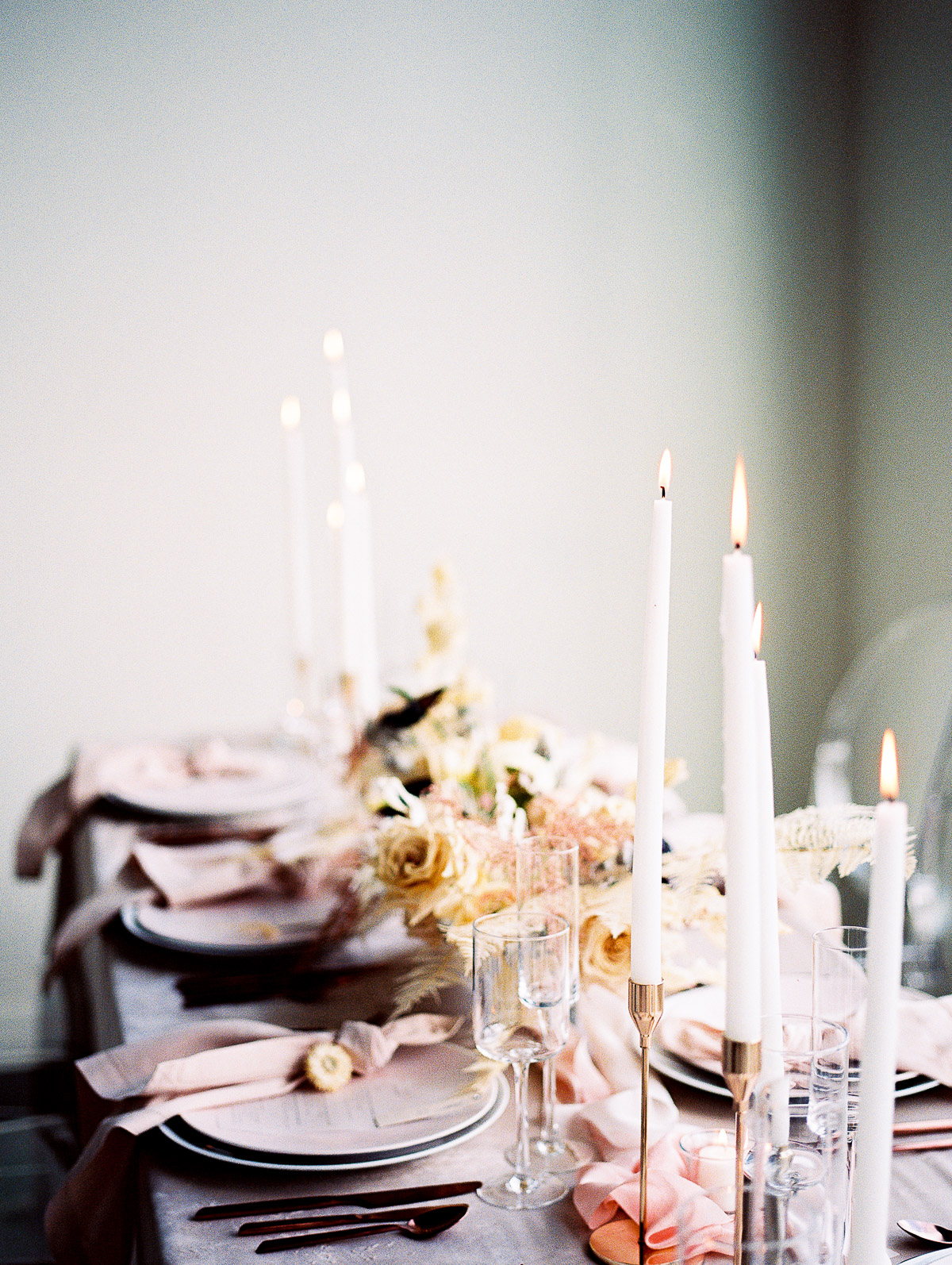A long table laid for wedding guests, with a gorgeous centerpiece and tall lit candles