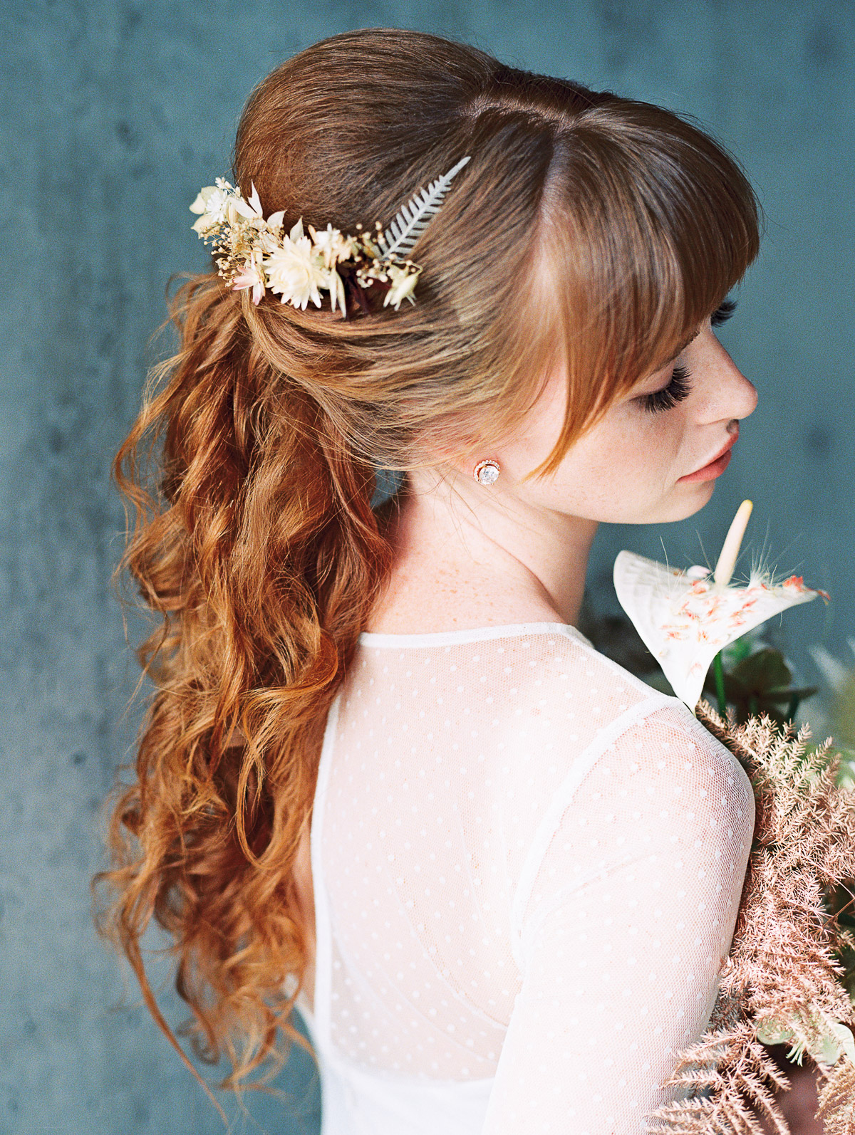 Detail shot of redhead brides winter updo, adorned with dried florals