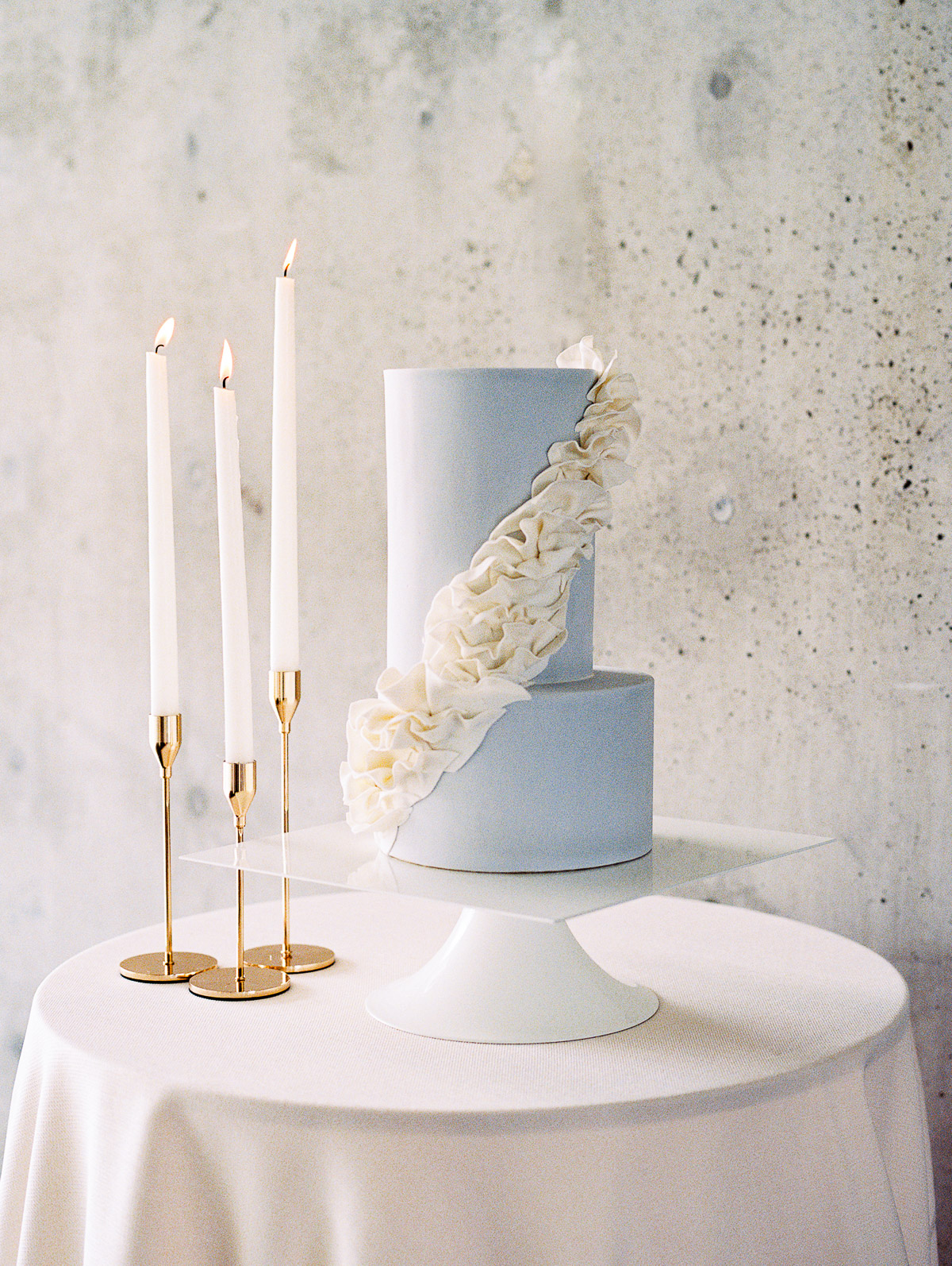 A modern and urban inspired wedding cake sits atop a well laid tables with tall candles