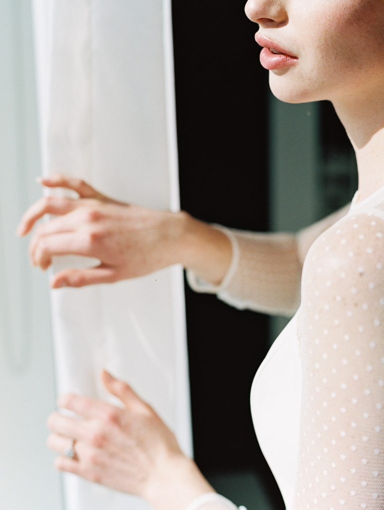 A bride stares out the window of her Jupiter Hotel room window before her wedding ceremony
