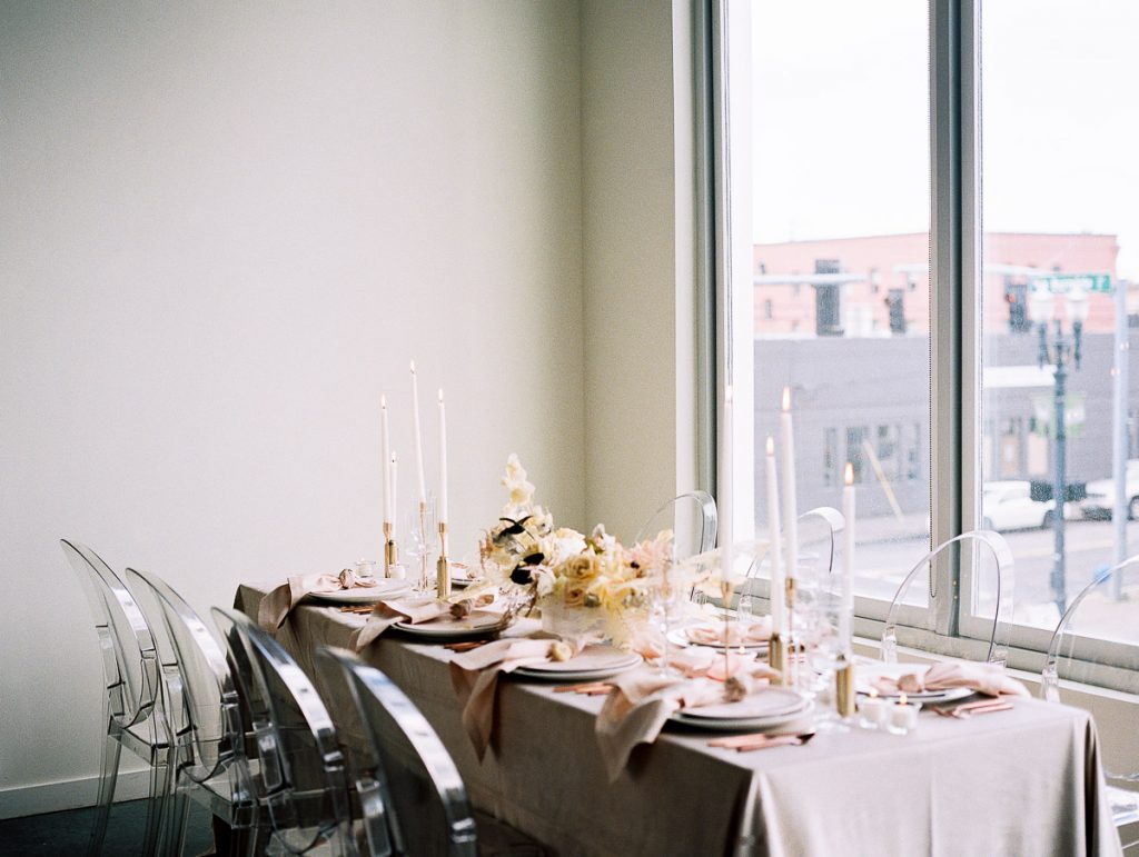Landscape shot of a long wedding table by the windows at Jupiter Hotel PDX