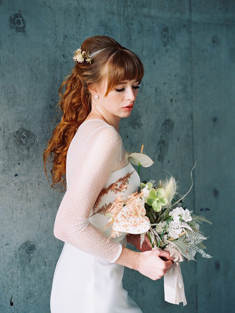 Bride looks down to observe her Wildflower Portland bridal bouquet