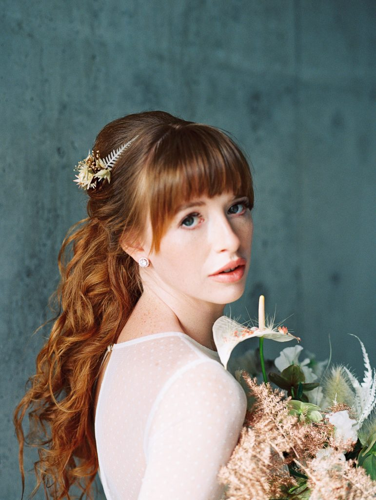 Bride holds her Wildflower Portland Bouquet close to her face and stares into the camera with a soft look