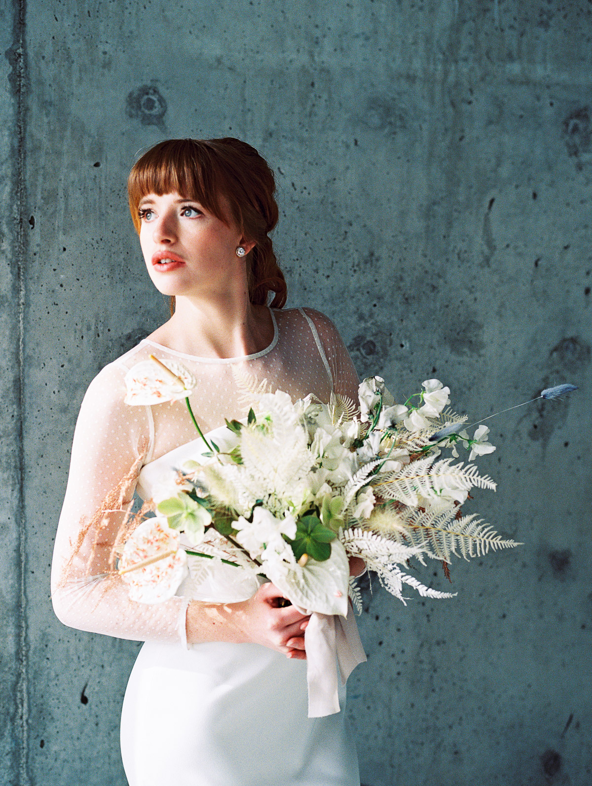 Bride stands in front of an industrial concrete wall for a bridal portrait by Portland Oregon Photographer, Kallie Dawn