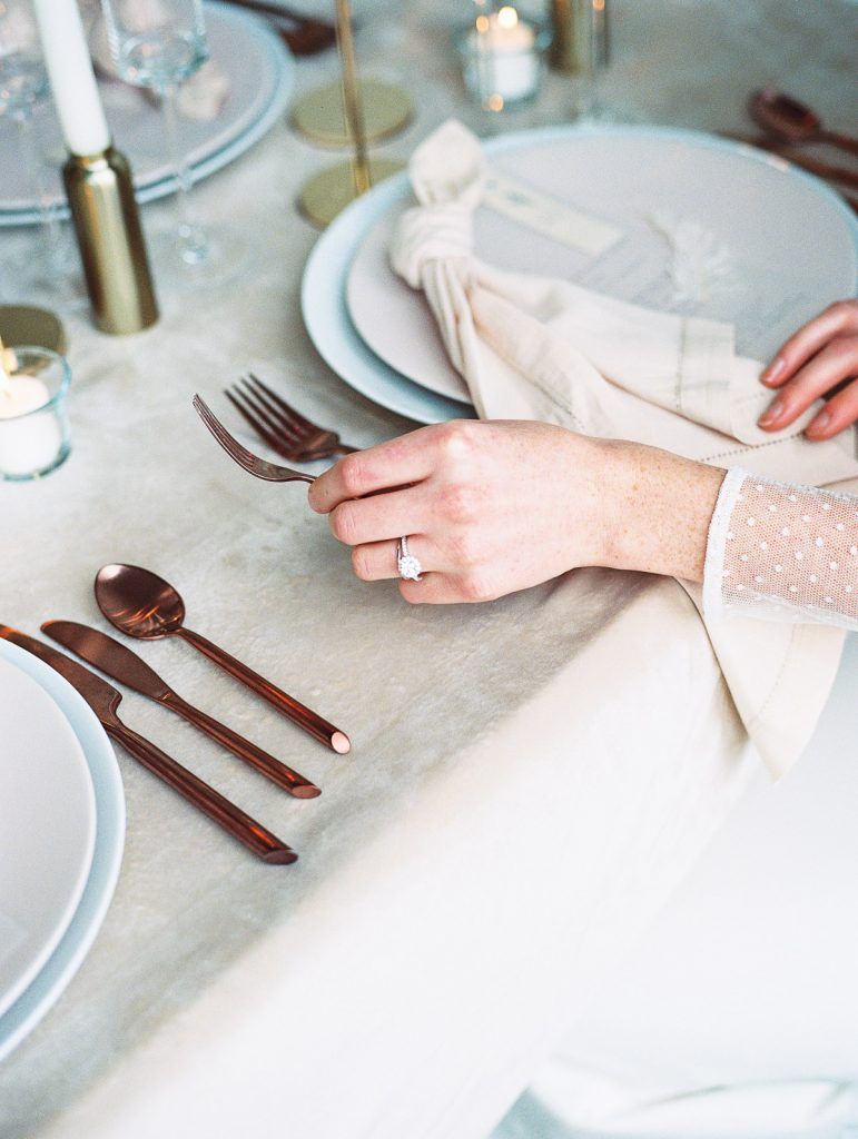 Bride reaches for her fork as she sits down for her wedding meal