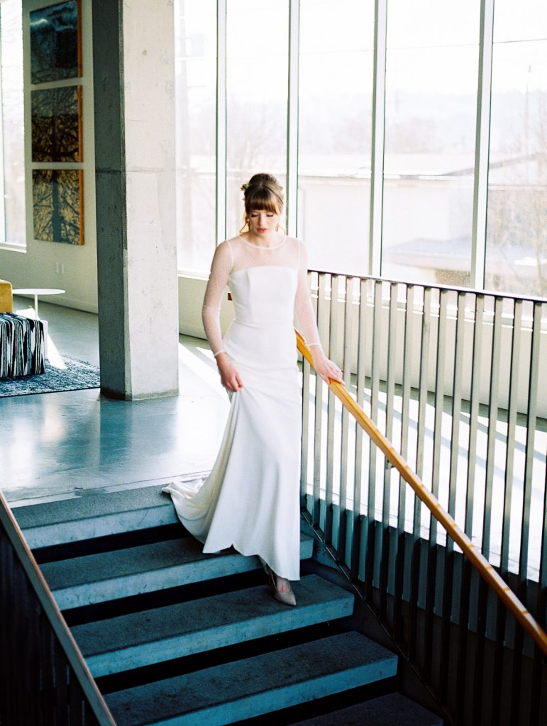 Bride makes her way down the stares of the Jupiter Hotel in Portland, as she exits her wedding celebration