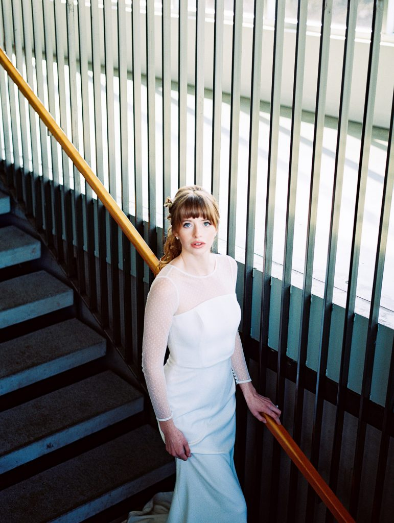 Bride stops to stare into the camera, mid-stair