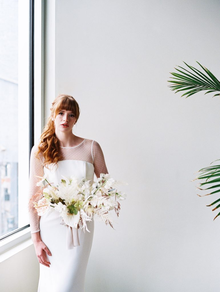 Strong portrait of a bride staring into the lens by a window, while a tropical plant pops into the frame