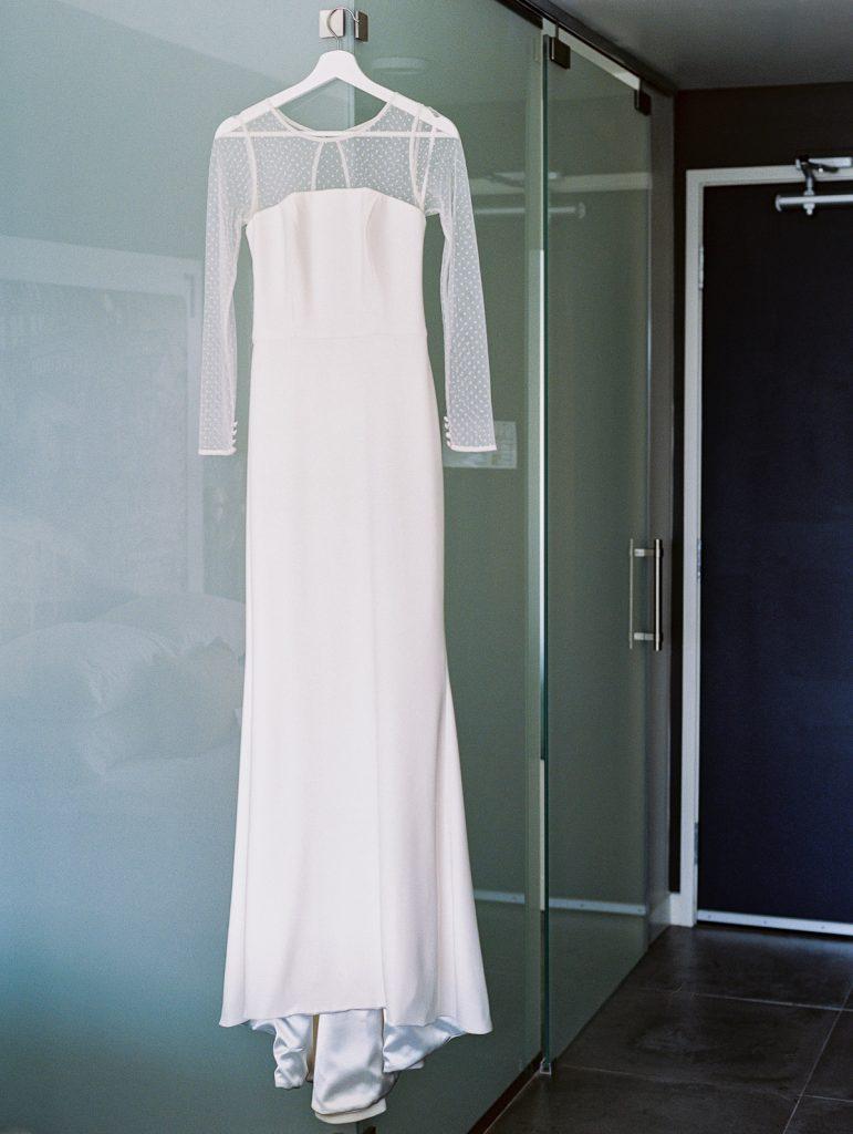 A bride's wedding dress hanging in her hotel room at Jupiter Hotel in Portland Oregon