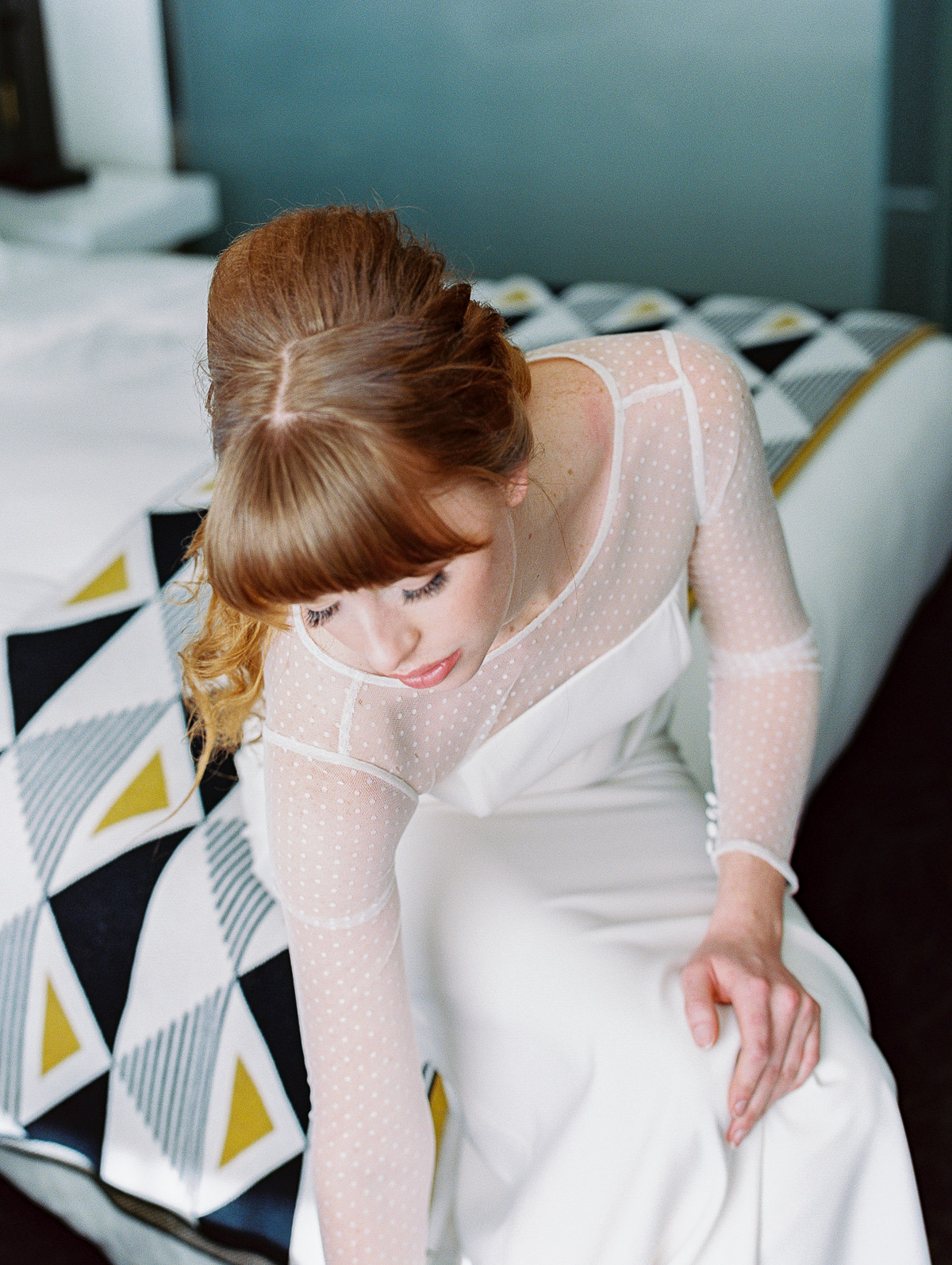 Redhead bride sitting in a modern suite at Jupiter Hotel, putting on her wedding shoes
