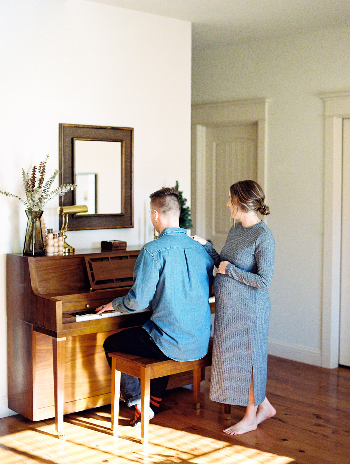 Oregon couple sits by the piano as the husband plays for his expecting wife